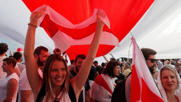 Manifestantes seguram uma bandeira gigante branca-vermelha-branca histórica da Bielorrússia durante um protesto contra os resultados das eleições presidenciais exigindo a renúncia do presidente da Bielorrússia, Alexander Lukashenko, e a libertação de prisioneiros políticos, em Minsk, 16 de agosto.