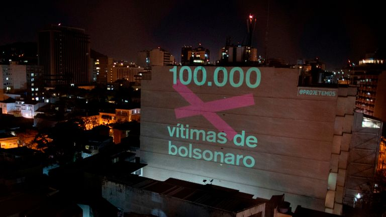 """TOPSHOT - A projection on a building honouring the 100,000 victims who died of the novel coronavirus COVID-19 in Brazil reads """"100,000 Victims of (Brazilian President Jair) Bolsonaro"""" as the country became the second in the world to pass the grim milestone, in Botafogo neighbourhood in Rio de Janeiro, Brazil, on August 8, 2020. - Just a day after Latin America and the Caribbean became the hardest-hit region in the global pandemic, Brazil reported a total of 100,477 fatalities, joining the United States as the only two countries to surpass the six-digit death mark. (Photo by Mauro PIMENTEL / AFP) (Photo by MAURO PIMENTEL/AFP via Getty Images)"""