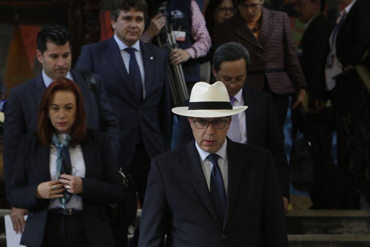 Chapman, de óculos, vestindo um terno escuro, gravata azul e chapéu panamá branco, desce um lance de escada, uma multidão de diplomatas e funcionários atrás dele.