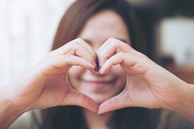 Mulher fazendo sinal de mão de coração | Foto Premium