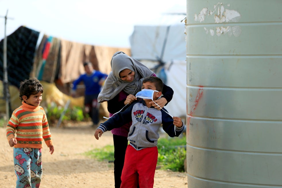 A Syrian refugee puts a mask on her child in southern Lebanon
