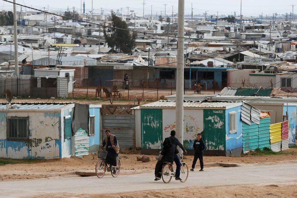 Syrian refugees ride their bikes in Zaatari refugee camp in Jordan