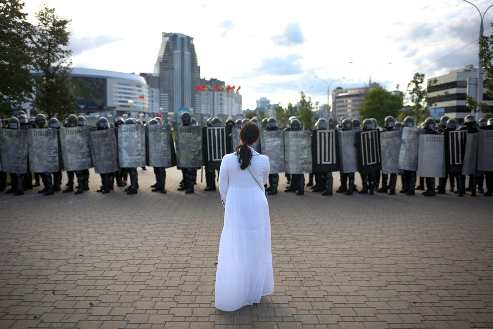 Uma mulher vestida de branco em frente a uma linha da polícia de choque durante uma manifestação de apoiadores da oposição bielorrussa protestando contra os resultados oficiais das eleições presidenciais em Minsk, Bielorrússia, 13 de setembro de 2020