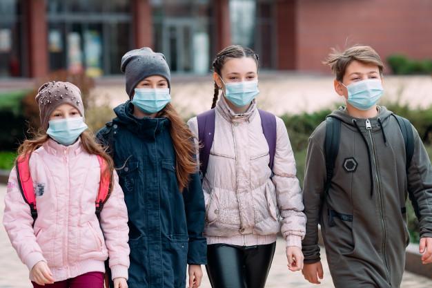 Crianças estudantes de máscaras médicas saem da escola. | Foto Premium