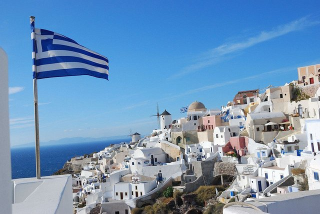 Casas e bandeira da Grécia em Oia, Santorini, Grécia. - Guia de Viagens