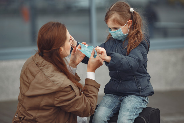 Free Photo | A european mother in a respirator with her daughter are  standing near a building.the parent is teaching her child how to wear  protective mask to save herself from virus